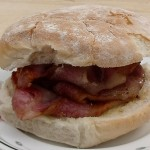big stack of bacon in a floury bread roll